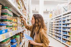 Young beautiful woman with a tablet carefully studying the composition of baby food, the girl chooses food in a. Supermarket Royalty Free Stock Photos