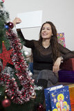 Young beautiful woman with tablet and Christmas tree Royalty Free Stock Image