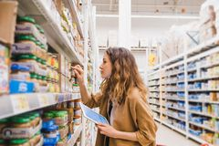 Young beautiful woman with a tablet picks baby food in a supermarket, the girl reads the composition of a product close. Up Stock Photography