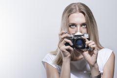 Young beautiful woman taking a photo with a retro camera Stock Image