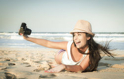Young beautiful woman taking photos on beach. With vintage camera Stock Photography