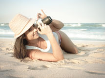 Young beautiful woman taking photos on beach. With vintage camera Royalty Free Stock Photography
