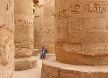Young beautiful woman taking pictures between the columns of the hypostyle hall of Karnak's temple in Luxor, Egypt.  Royalty Free Stock Photos