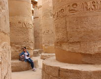 Young beautiful woman taking pictures between the columns of the hypostyle hall of Karnak's temple in Luxor, Egypt.  Stock Photography