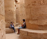 Young beautiful woman taking pictures between the columns of the hypostyle hall of Karnaks temple in Luxor, Egypt Stock Photography