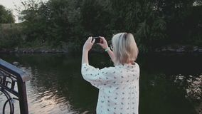 Young beautiful woman taking pictures with her smartphone in the city park near the lake stock video