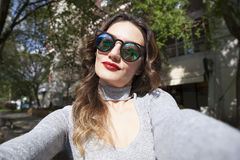 Young beautiful woman taking self portrait selfie outdoors Royalty Free Stock Photography