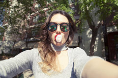 Young beautiful woman taking self portrait selfie outdoors Royalty Free Stock Images