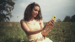 Young beautiful woman taking selfie on phone while sitting on grass. stock footage