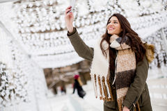 Young beautiful woman taking selfie photo in winter snow park. View of the young beautiful woman taking selfie photo in winter snow park Stock Photo