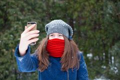 Young beautiful woman taking selfie photo in winter snow park. Walking in a winter park and having fun on a cold sunny day Stock Photo