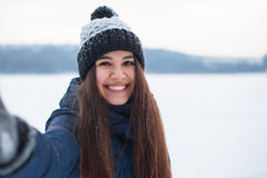 Young beautiful woman taking selfie photo in winter snow park. Walking in a winter park and having fun on a cold sunny day Stock Images