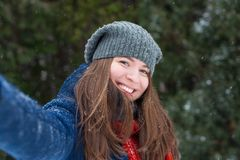 Young beautiful woman taking selfie photo in winter snow park. Walking in a winter park and having fun on a cold sunny day Stock Photography