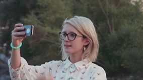 Young beautiful woman taking selfies with her smartphone in the city park near the lake stock footage