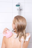 Young beautiful woman taking shower with sponge Royalty Free Stock Photos