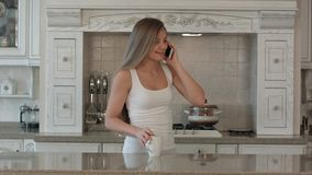 Young beautiful woman talking cell phone, drink coffee or tea in the kitchen, happy smile stock image