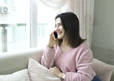Young beautiful woman talking by mobile phone on couch. royalty free stock image