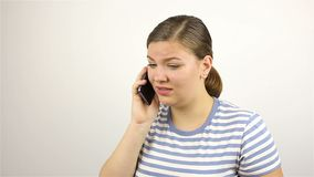 Young beautiful woman talking on the phone. bad news. Grey background stock video