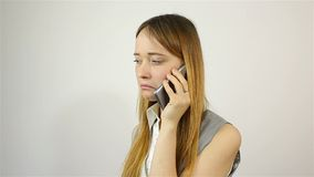 Young beautiful woman talking on the phone. bad news. Grey background stock video footage