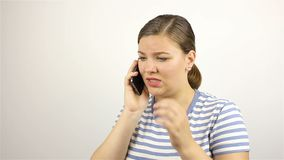 Young beautiful woman talking on the phone. bad news. Grey background stock footage