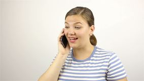 Young beautiful woman talking on the phone. Grey background stock video