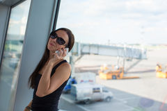 Young beautiful woman talking on the phone while Stock Photography
