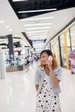 Young beautiful woman talks by a mobile phone in shopping mall. Young beautiful woman talks by a mobile phone in shopping mall background Royalty Free Stock Image