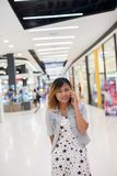 Young beautiful woman talks by a mobile phone in shopping mall. Young beautiful woman talks by a mobile phone in shopping mall Stock Image