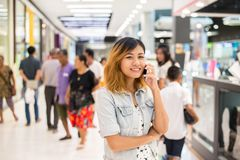 Young beautiful woman talks by a mobile phone in shopping mall. Young beautiful woman talks by a mobile phone in shopping mall background Stock Photo