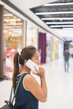 Young beautiful woman talks by a mobile phone in shopping mall. Young beautiful woman talks by a mobile phone in shopping mall background Royalty Free Stock Images