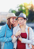 Young beautiful woman telling secret to her friend in the city Stock Photo