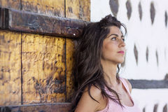 Young beautiful woman thinking against wooden door Stock Photo