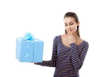Young beautiful woman thinking about gift box holding it Royalty Free Stock Photos