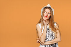 Young beautiful woman thinking looking to the side at blank copy space, over orange background stock image