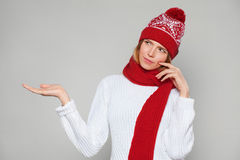 Young beautiful woman thinking looking to the side with showing open hand palm at blank copy space, Christmas girl wearing knitted Royalty Free Stock Images