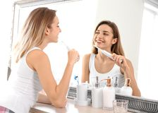 Young beautiful woman with toothbrush near mirror in bathroom. Personal hygiene stock photos