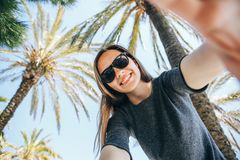 Young beautiful woman tourist or blogger makes a selfie or is reporting to its subscribers on the background of palm. Trees in a hot country Stock Images