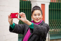 Young beautiful woman tourist taking pictures on mobile phone Stock Images