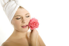 Young beautiful woman in towel with pink flower Royalty Free Stock Images