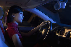 Young beautiful woman in a traditional Chinese dress driving at night Stock Image