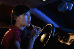 Young beautiful woman in traditional Chinese dress putting on lipstick in the rear view mirror of the car at night Royalty Free Stock Photography