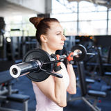 Young beautiful woman training biceps with barbell Royalty Free Stock Images