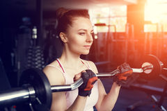 Young beautiful woman training biceps with barbell. Young beautiful woman doing biceps curl with EZ curl bar in a gym. Athletic girl doing workout in a fitness stock photography