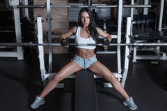 Young beautiful woman is training in the gym with a barbell Royalty Free Stock Photos