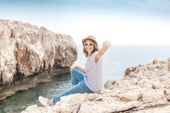 Young beautiful woman travel girl in hat and sunglasses sits on. A rocky seashore, summer vacation and travel, sunny portrait Stock Photos