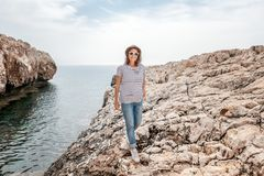Young beautiful woman travel girl in hat and sunglasses walking. Along the rocky seashore, summer vacation and travel, sunny portrait Stock Photography