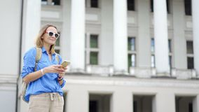A young beautiful woman traveler with a backpack, using her smartphone stock footage