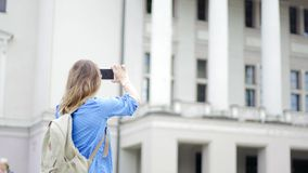 A young beautiful woman traveler taking a photo of the historical building stock video footage