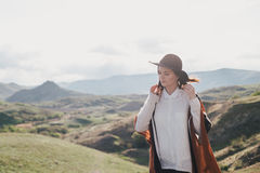 Young beautiful woman traveler wearing hat and poncho relaxing on the top of the hill Royalty Free Stock Photography