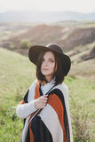 Young beautiful woman traveler wearing hat and poncho relaxing on the top of the hill Royalty Free Stock Photos